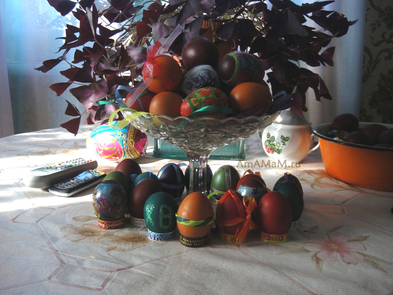 Ваза с пасхальными яйцами и крашеные яички на подставках - фото