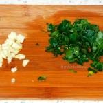 Чеснок и зелень на разделочной доске - фото