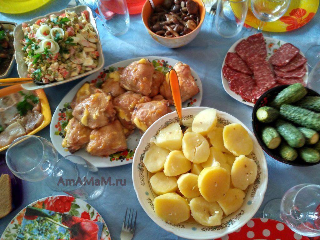 Маслята, курица, малосольные огурцы, картошка, салат на праздничном столе