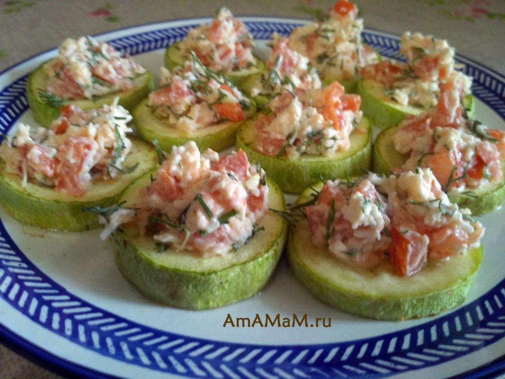 Запеченные кабачки, с разложенным на них салатом из сыра и помидоров с чесноком