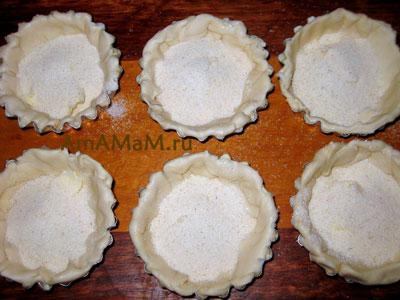Выкладываем тесто в формочки, сверху слегка посыпаем маслом и манкой