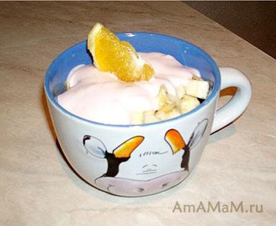 Вкусный фруктовый салат из банана, яблока, груши и апельсина, заправленный сливочным йогуртом и украшенный апельсиновой долькой