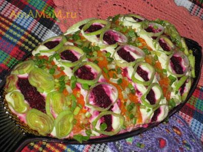 Готовый слоеный салат - Селедка под шубой, украшенная луком-пореем