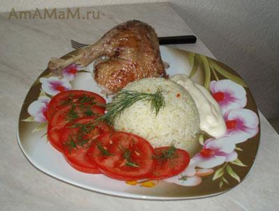 Кусочек очень вкусной утки, тушеной в пиве с гарниром из риса и свежих помидоров