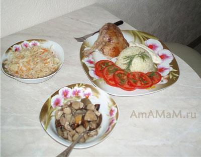 Утка в пиве, тушеная с начинкой из яблок, выложена на тарелку. ПОдается с гарниром из риса, помидоров и со вкусными закусками: квашеной капустой и грибами