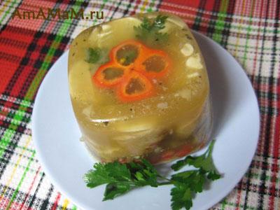 Холодец из свиных ушек, украшенный паприкой, лимоном и зеленью, вид сверху
