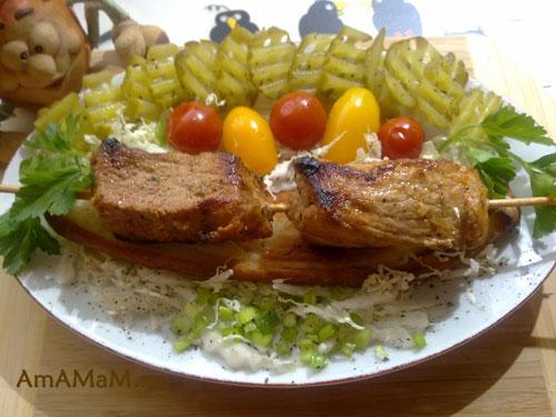 Готовое испанское блюдо из свинины. жареной на шпажках в сковороде