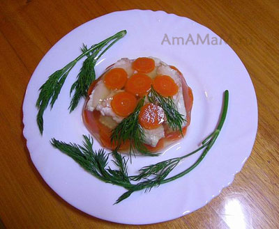 Готовое рыбное заливное из пикши, украшенное вареной морковкой, лимоном и зеленью